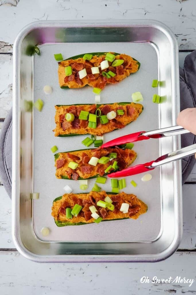 4 jalapeno popper halves on a tray, using tongs to pick one up