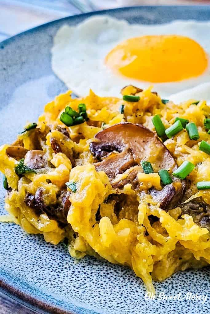 Buttery Garlic Mushroom and Chive Spaghetti Squash on a plate with a fried egg