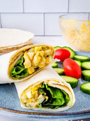 Creamy Ranch Egg Salad Wrap cut in half, on a plate with cucumber slices and cherry tomatoes.