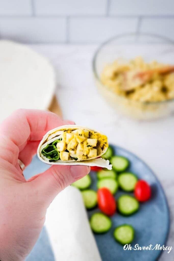 Hand holding a cut egg salad wrap
