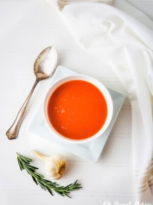 Overhead shot of garlic rosemary tomato soup in a white bowl