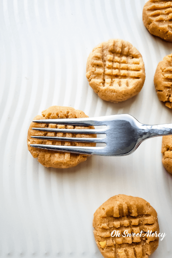 Making criss cross pattern with a fork on Easy No Bake Peanut Butter Cookies.