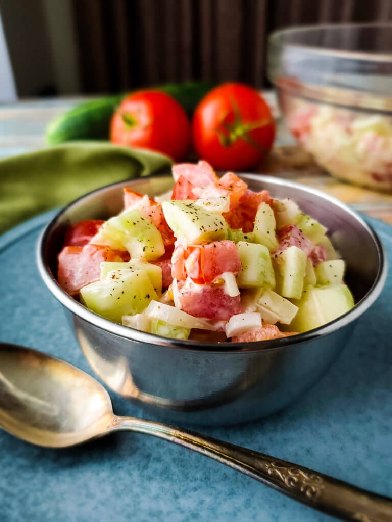 Close up photo of Creamy Cucumber Tomato Salad in a bowl.