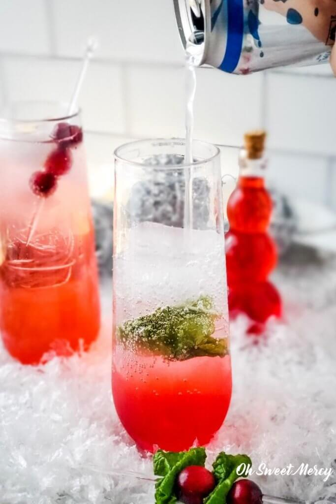 Pouring sparkling water into cranberry mocktail