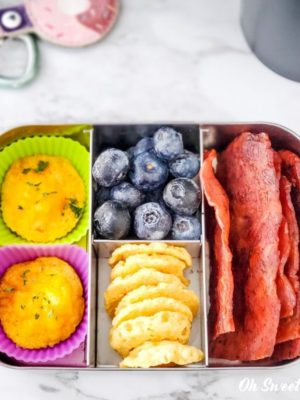Breakfast on the go snack box - egg puffs, blueberries, cheese crisps, cooked turkey bacon.