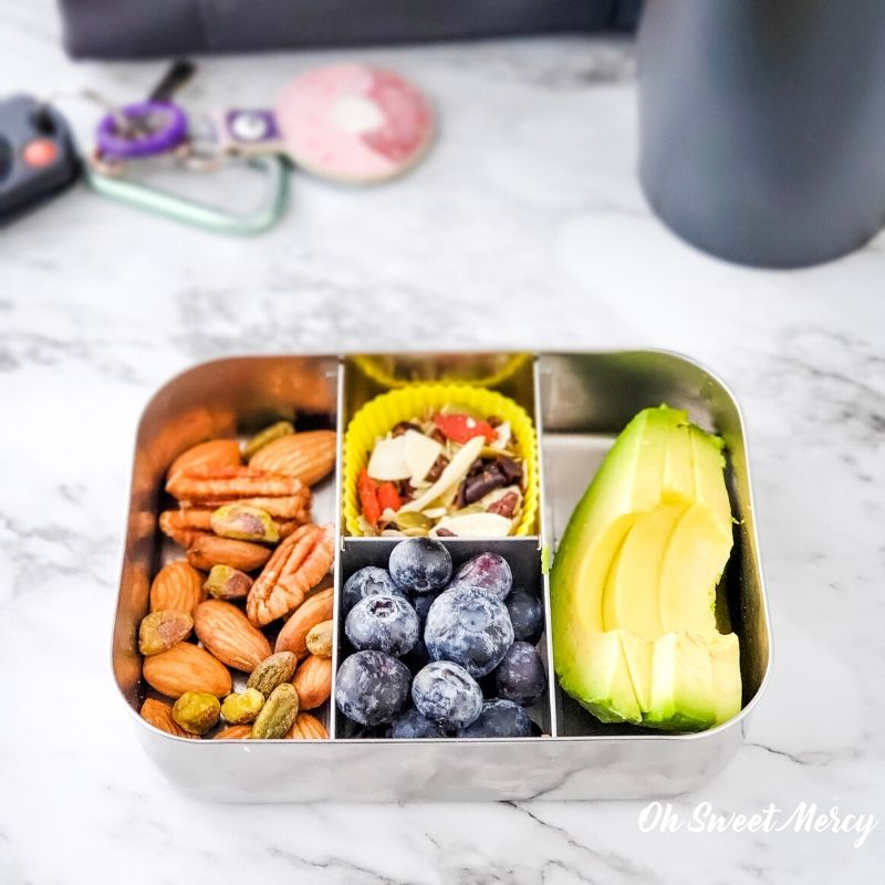 Vegan protein and healthy fats snack box - mixed nuts, unsweetened trail mix, blueberries, avocado slices.