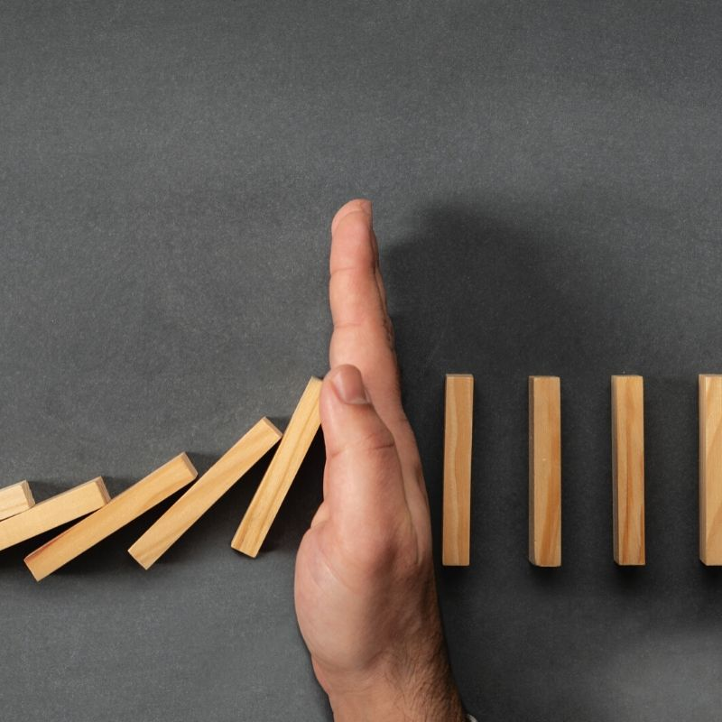 hand stopping falling dominoes