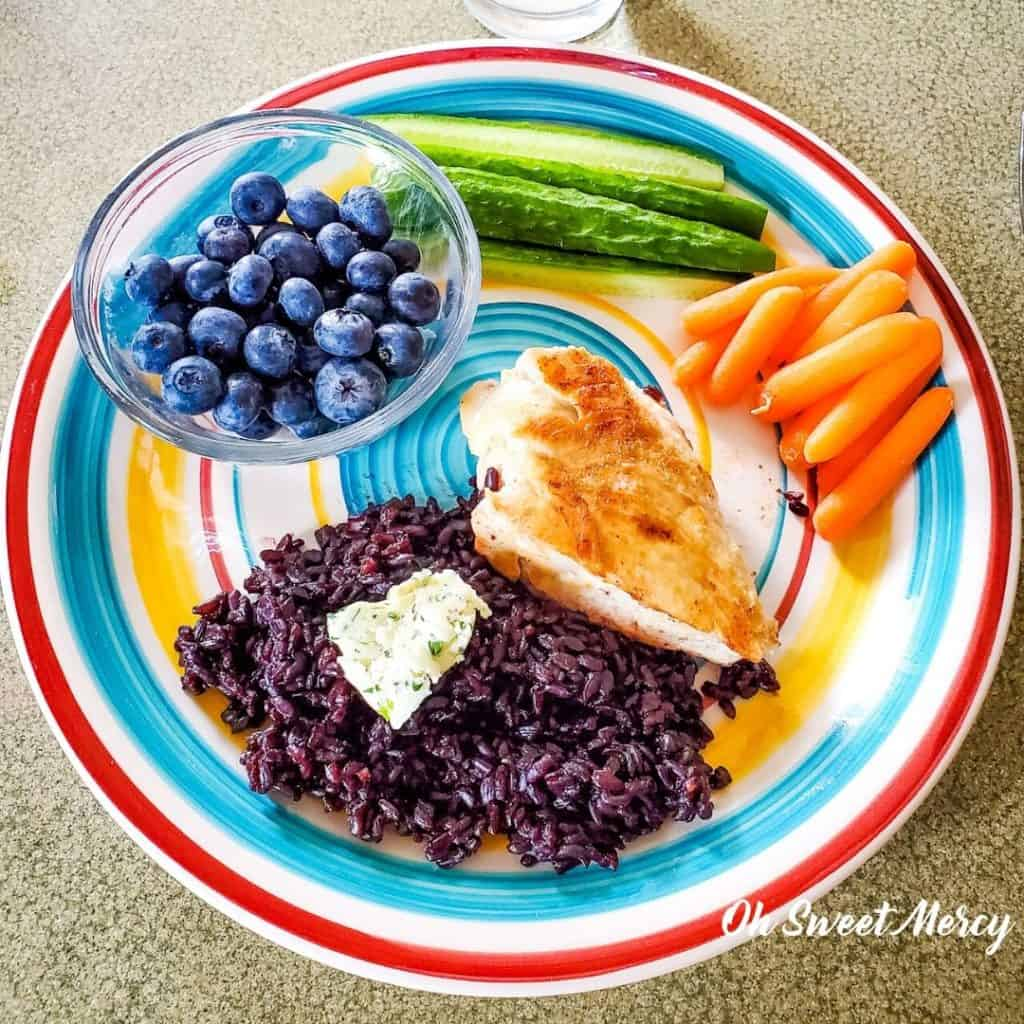 Colorful plate of grilled chicken, fresh cucumbers, carrots, cooked black rice, pat of herbed butter and fresh blueberries