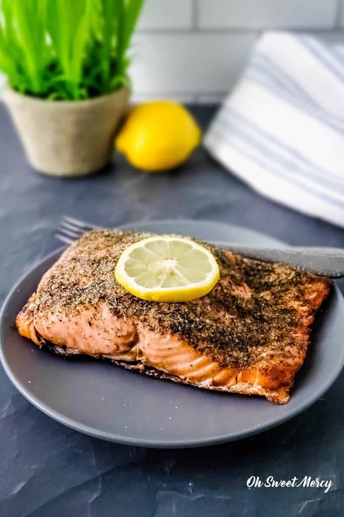 Lemon Dill Air Fryer Salmon on a gray plate with slice of lemon on top.