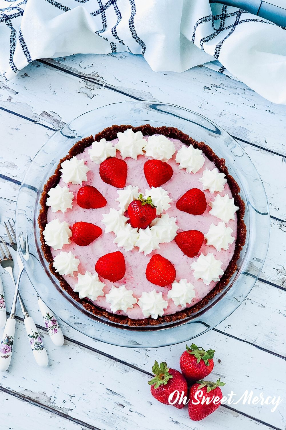 Whole low carb strawberry freezer pie decorated with dollops of whipped cream and strawberry halves