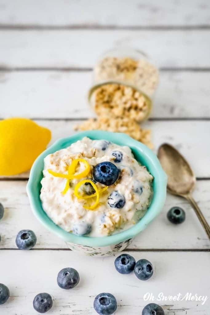 Bowl of overnight oats garnished with blueberry and lemon zest.