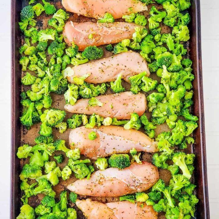 Seasoned chicken and broccoli on baking sheet