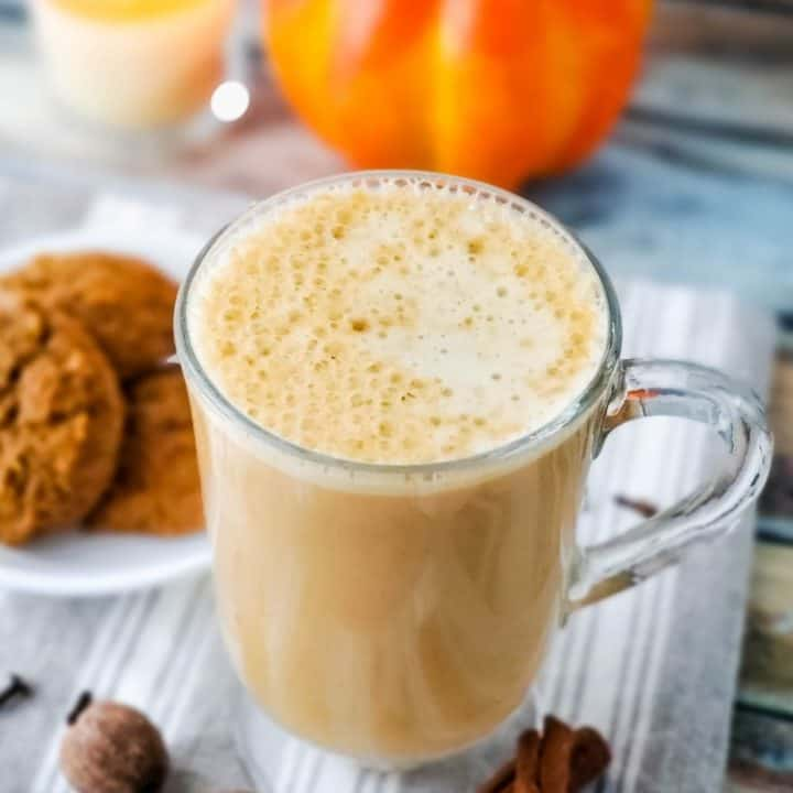 Beverage in clear glass mug with plate of cookies