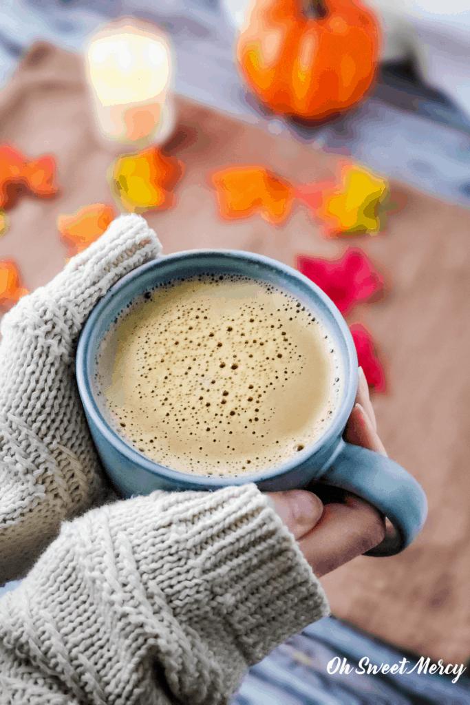 Cozy sweater around hands holding a mug of warm, creamy pumpkin spice steamer