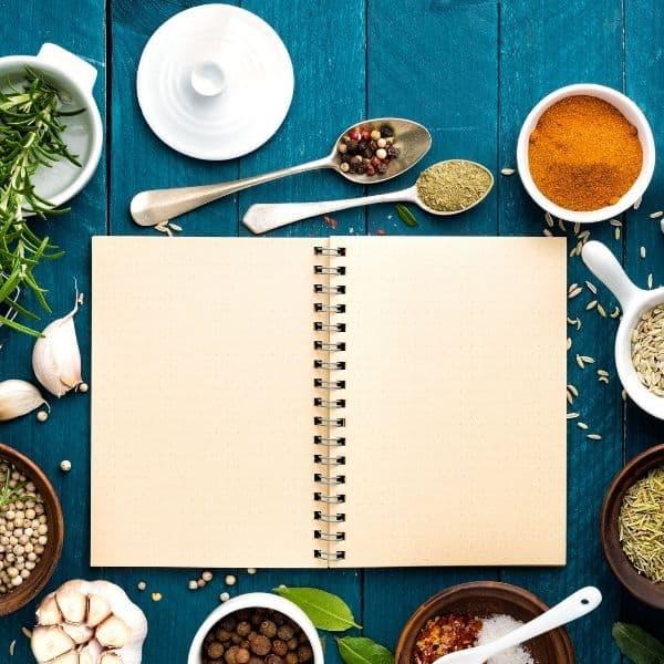 blank notebook surrounded by spices on blue background