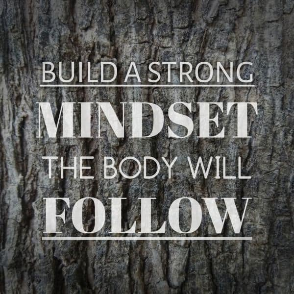 "Quote: ""Build a strong mindset the body will follow"" on a tree bark background"