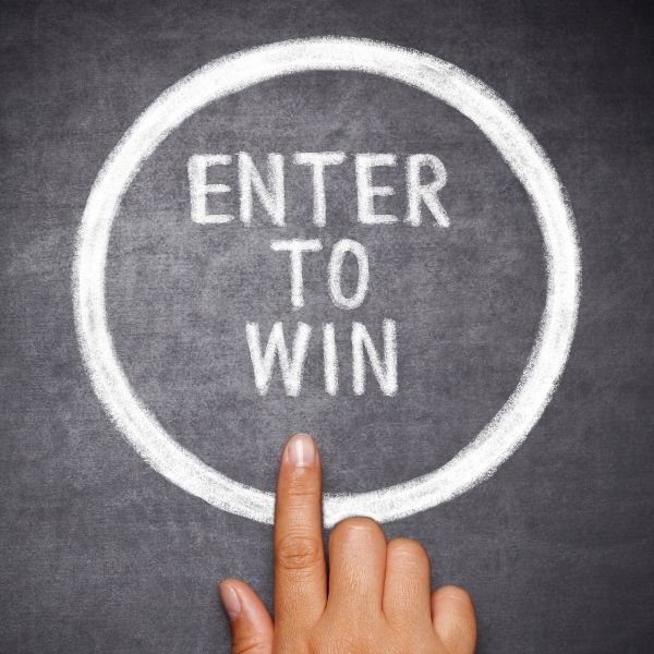 "finger pointing at ""enter to win"" written on chalkboard"