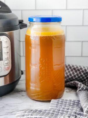 Jar of smoked turkey broth beside an Instant Pot