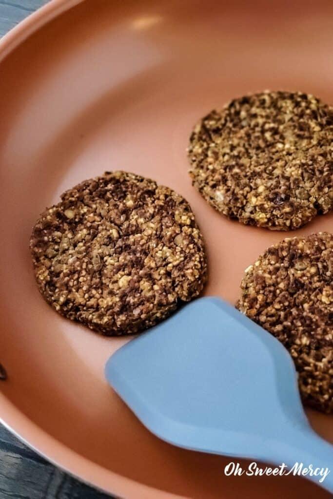 cooking lentil burgers in copper ceramic skillet