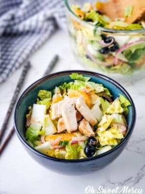 Close up of bowl of salad with chicken.