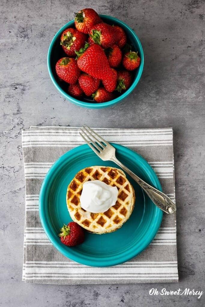 Overhead shot of waffles on aqua plate topped with yogurt, bowl of strawberries