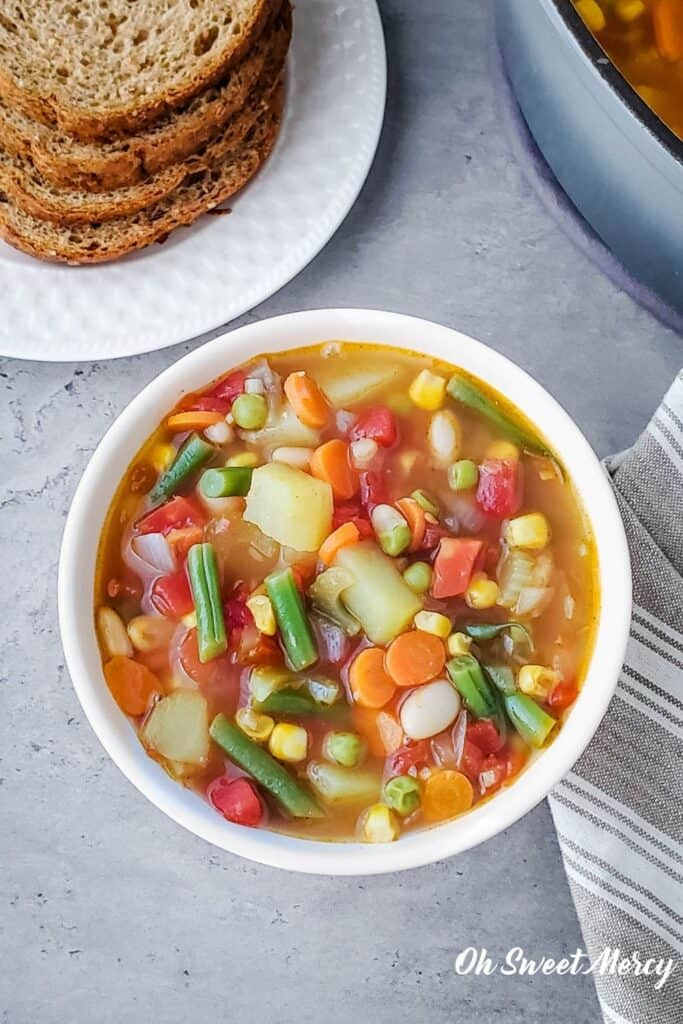 Bowl of homestyle vegetable soup with bread on a plate.