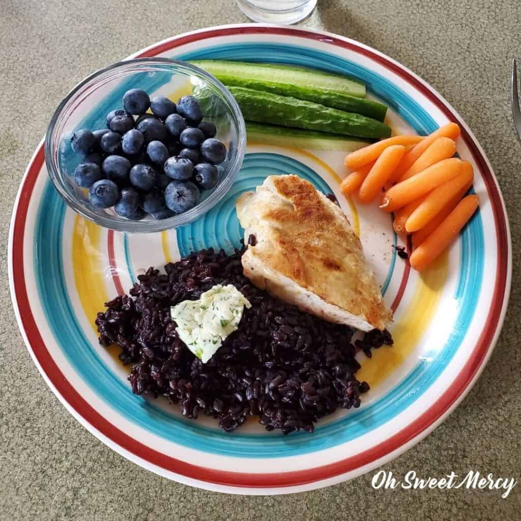 Plate of simple THM E meal example: black rice, chicken breast, carrots, cucumbers, blueberries.