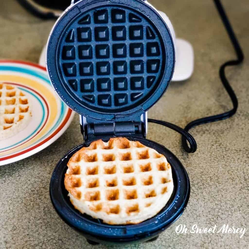 Cooked mini waffle in the waffle maker with lid open