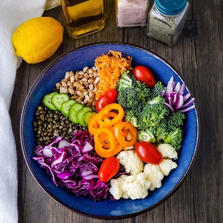 Bowl with grain bowl ingredients, lemon, olive oil, salt and pepper
