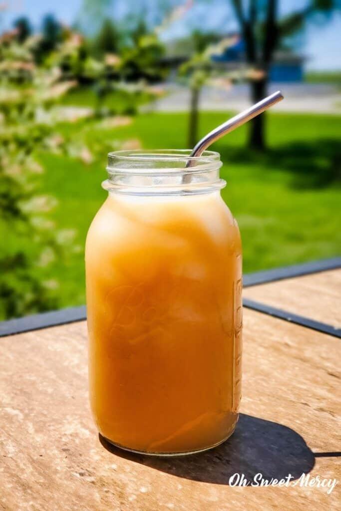 Mason jar of Creamy Coconut Oolong Iced Tea outside on a sunny day