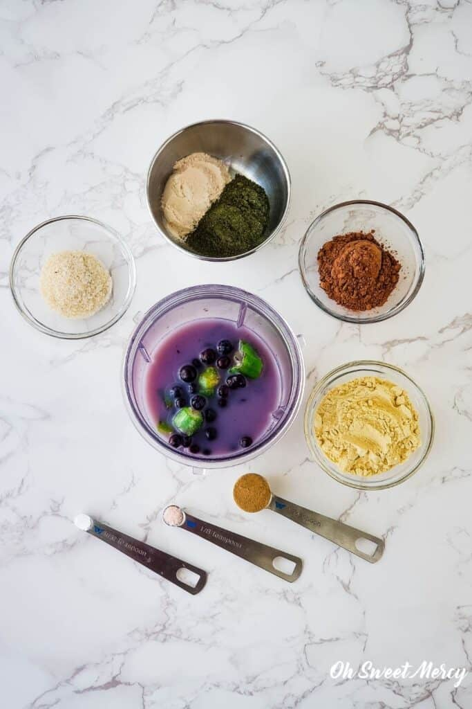 Overhead shot of blender cup with nut milk, blueberries, and okra, surrounded by psyllium husk, baobab, Dynamic Duo Greens Powder, cacao powder, vegan protein powder, camu camu powder, salt, and stevia.