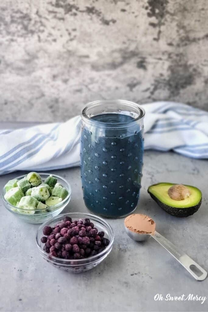 Glass of my Chocolate Blueberry Smoothie (AKA The Breakfast Smoothie) with some ingredients that are in it: blueberries, okra, cacao powder, avocado