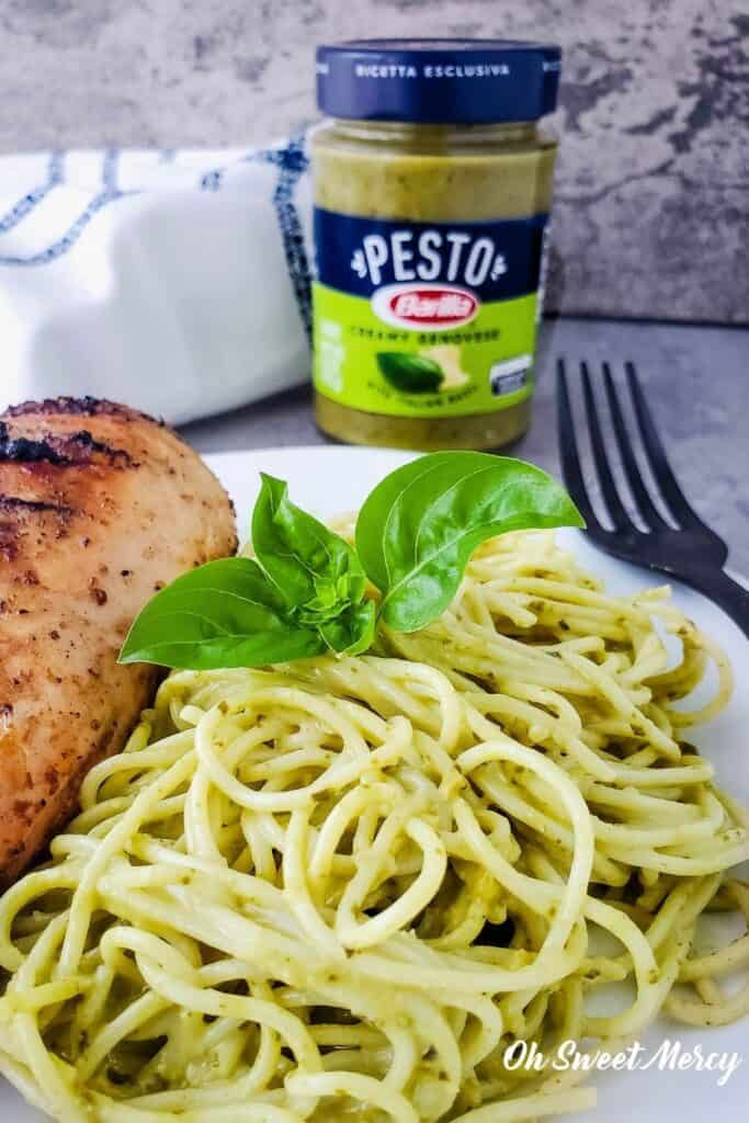 Photo of pasta and grilled chicken with jar of Barilla Creamy Genovese Pesto in background