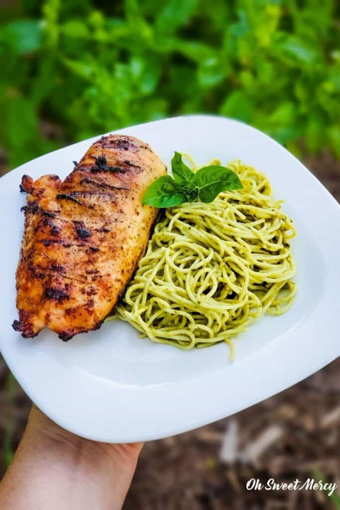 Plate of grilled chicken and pesto pasta made with Barilla Creamy Genovese Pesto.